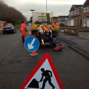 Council workmen and roadworks sign