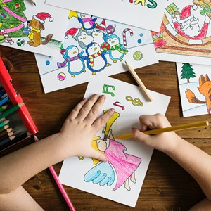 Child's hands colouring in picture on desk with pencils
