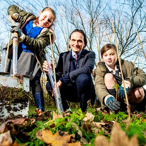 Image shows Cllr Adam Clarke planting trees with Montrose Primary School pupils